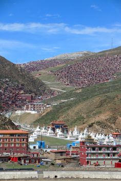 Glimpsing Larung Gar Monastery from the highway to Serda.   About 20km from the town of Serda, Larung Gar Monastery is famous for the thousands of little red houses that cling to the hillsides up a steep valley.   Home to 40,000-50,000 monks and nuns, Larung Gar is the biggest Buddhist settlement in the world.