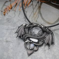Dragon...  The necklace is made of tin, obsidian, hematite and moonstone  The dimensions of the pendant are 80 x 70 mm The jewel is hung on a 18