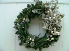 A holiday show stopper! Evergreen wreath with sophisticated, classy sparkling starfish, shells, sand dollars and flocked greenery (all artificial). The leaves are shimmery silk and the leaves and pine cones are iridescent silver. I shimmered the shells with Martha Stewart sparkles. Amazing in person!!!!    Measurements: Base 21 around. From tip to tip, allow 7 in depth. May be displayed outdoors if protected from the elements. Best is to display this holiday wreath inside. There is only one…