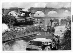 U.S. troops in action near Coutances = [Jeeps, camions et chars se croisent au pied du viaduc ferroviaire dynamité par les allemands].