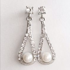 Luxurious pearl earring Crafted with the utmost magnificence, this pearl and crystal earring is a must have for women who aims glamorous glow in their ensemble. Made from sparkling crystals in elliptical shape dangle with a beautiful millimeter off white pearl in the center. Expect to take everyone's breath away Jewelry Earrings