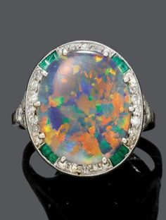 BLACK OPAL, EMERALD AND DIAMOND RING, ca. 1920. Set with one black opal weighing 4.60 cts, with blue, green, yellow, orange and red colours, surrounded by calibré-cut emeralds and circular-cut diamonds, mounted in platinum. #ArtDeco #Ring