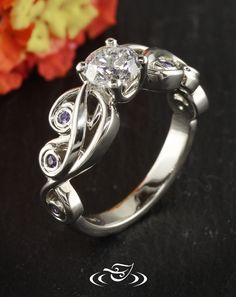 Beautiful Custom 14kt warm white gold mounting holding a prong set  1.01ct diamond center stone. Organic pierced curling design that stops half way down shank with purple sapphire melee side stones bezel set in curls.
