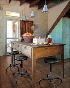 love everything about this kitchen from the wood island to the turquoise door to the old stone wall to the metal stools!