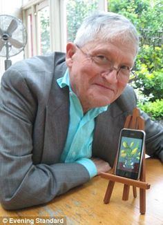 David Hockney at table with art created on his iphone .