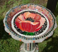 Poppy Birdbath Small mosaic birdbath with a large poppy center. The base has mosaic detail up the pedestal and around the foot section. Can be done in a custom design and colors