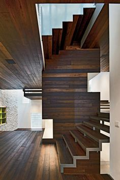 Maison Escalier - The kitchen and bathrooms are contained in the stair core. Locust-wood paneling on the floors, ceilings, and stairs contrasts with whitewashed masonry walls.