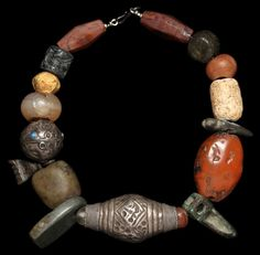 by Marion Hamilton | Necklace; central bead is Afghani silver, prehistoric amazonite and other stones, orange carnelian, Afghani schist seal, Hittite bronze amulets || 3'000$