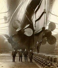 Men stand with the drydocked RMS Mauretania, 1906 Photo/ www.machinejunky.com