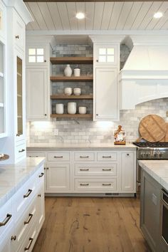 Love the white cabinets marble subway tiles and wood open shelving between cabinets