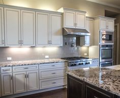 Leander Texas Kitchen with Merillat white distressed cabinets and oversized granite island!