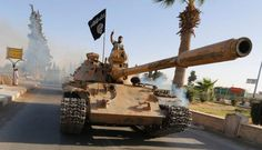 Militan ISIS di atas tank dalam parade militer di sepanjang jalan provinsi Raqqa utara, 30 Juni 2014