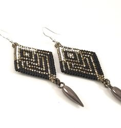 Handmade diamond shaped beaded earrings, inspired by the Black Widow. Steel finished hex cut beads in defining lines are eye-catching against the black matte and pearl white. The focal bead is a gun metal drop bead which adds the glamour with a little edge. The Earwire is 99.9% pure Silver Plated and nickel free. Just over 3 inches from top of the ear wire to the bottom of the metal drop bead and 1.2 inches in width.