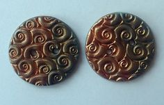 Handmade polymer clay buttons with a deep swirl texture highlighted with 2 colours of mica powder bronze and copper for an eye catching look. Add