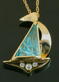 Dreamscape™ cut Sail Shape Blue Topaz cut by John Dyer & Co.  Sailboat pendant designed and made by Crown Trout Jewelers  using 14k Gold & white Sapphires.