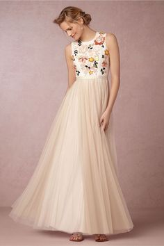 Modern wedding dress with blush pleated skirt and bodice with flowered, beaded embroidery.