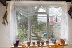 Shabby chic, country cottage farm style kitchen, net curtains tied up with ribbon, you can just see the train whipping past at the end of the garden