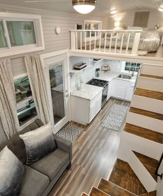 The kitchen features white cabinetry, granite counters, upper shelving for storage, pantry, full size side-by-side stainless steel refrigerator, propane cooktop/oven, oversize sink with commercial faucet, and glass tile backsplash.