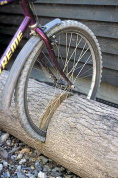 Gebruik een omgezagen boomstam als fietsenrek door er gleuven in te zagen. Dit is toch vele mooier dan zo een saai ijzeren fietsenrek?