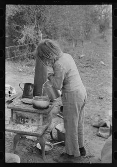 1939 - Child of white migrant adding water to boiling beans on stove which was set up immediately after reaching camping grounds near Harlingen, Texas