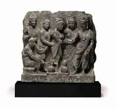 A rare gray schist relief with the marriage of Siddhartha  Gandhara, 2nd/3rd Century  With Siddartha at right, dressed in a sanghati and adorned with princely jewels facing Yasodhara at center, herself dressed in a long sanghati and fanned with a palm leaf by a female attendant figure, with three further figures at left, including a seated Brahmin who tends the flame and water jugs at the couple's feet 8½ in. (21.6 cm.) wide