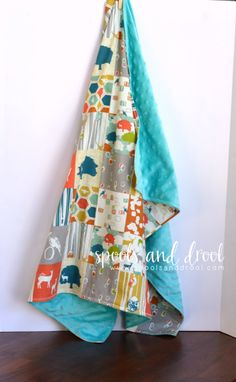 The Woodland Patchwork is made from 100% organic cotton from Birch Fabrics. The patchwork displays colorful and artistic woodland scenes such as bold trees, majestic deer, and mischievous animals in tree knots! The back is the softest minky on the planet in a beautiful aqua color.