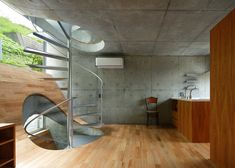 Spiral stairs puncture hilly floors in house by Takeshi Hosaka
