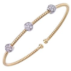 Simplistic and elegant, this yellow gold bangle features three white gold diamond stations. It stacks beautifully with the matching white and rose gold bangles.
