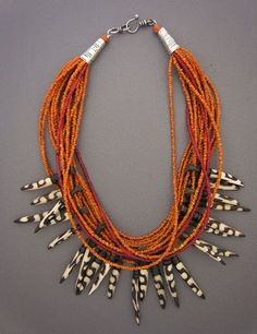 by Anne Holland |  Contemporary Batik bone spears from Kenya dangle playfully below 17 strands  of tiny and exquisite antique Indonesian glass beads. |  Dorje Designs | Sold or No longer availabe