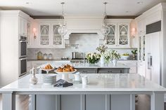 Fun white kitchen design with white kitchen cabinets, calcutta marble counter tops, pleated tapered drum island pendants, marble tiles backsplash, espresso counterstools and pot filler. Kitchen Island With Cooktop, Double Island Kitchen, Island Cooktop, Kitchen Countertops, Kitchen Cabinets, Kitchen Islands, Marble Countertops, White Cabinets, Upper Cabinets