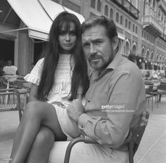 Italian actor Ugo Tognazzi, sitting on a chair outside a cafe, the singer and actress Marisa Solinas wearing a lace dress sitting on his knees , Lido, Venice, 1967.
