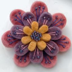 A beautiful, feminine brooch made from 3 layers of scrumptiously soft wool felt.Embroidered and beaded with matt rainbow-effect seed beads, and firmly attached to a 1 Brooches Handmade, Handmade Flowers, Handmade Crafts, Fabric Brooch, Felt Brooch, Brooch Pin, Felt Embroidery, Felt Applique, Felt Flowers