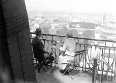 A couple enjoys a nice bottle of wine and a breathtaking view from the Eiffel Tower in 1928.