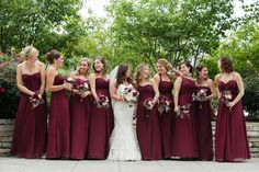 A bride and her many bridesmaids, dresses in long dark red dresses