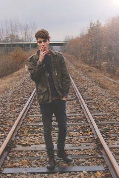 laid back posture. fashionable clothing and is smoking a cigarette which can come across as being cool. The fact he is on a train track suggests he doesn't care and shows danger