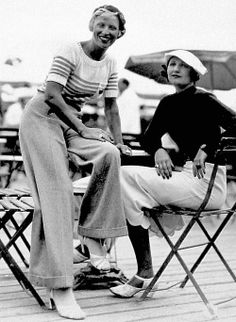 "Two 1930's ladies (wearing ""slacks!"") at a cafe near the beach. At that time, during the 1930's, Katherine Hepburn was wearing ""trousers"" when it was scandalous to do so! These girls may have thought if it was good enough for ""Kate"", then it was surely good enough for them! :)"