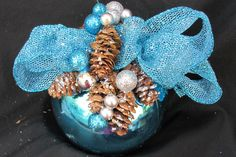 Turquoise ornament decorated with pine cones and miniature ornaments