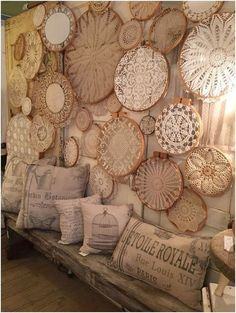 Embroidery hoops with doilies make up a collection to cover a wall. Various sizes scattered along the wall give it a different look that looks pretty. I love the pillows on the bench also.