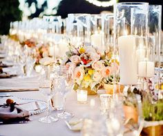 A romantic tabletop feautres link pink blooms lit by the string lights that hover above.