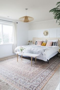 Boho master bedroom featuring pinks, greys and light woods.