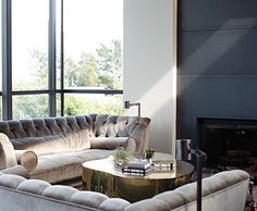 A custom silvery velvet tufted sofas surround a gold coffee table.