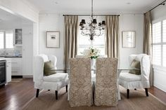 Chic, sophisticated, dining room with glass top white X base dining table, white wingback slipcover captain dining chairs, taupe damask slipper dining chairs, green pillows, sisal rug and silk taupe curtains window panels.