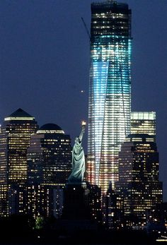 Statue of Liberty and One World Trade center in Red, White and Blue for the 4th of July. (Photo: Julio Cortez / AP)