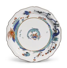 A rare Meissen Kakiemon lobed dish, circa 1730-35 painted in the so-called 'flaming tortoise' pattern, with a central coiled dragon, the shaped brown-edged rim decorated with a border of cranes, a pine-tree, bamboo, flowering plants and a mythical creature, crossed swords mark in underglaze-blue, incised / mark,