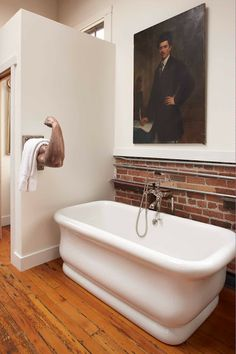 "The tub is from Waterworks. ""The arm is one of my absolute favorite things,"" said Fulk. He found it at March long ago. ""I swore I would someday use it as a towel rack.""  The nineteenth-century French oil portrait was acquired from antiques dealer Stephane Olivier at the Clignancourt flea market in Paris."