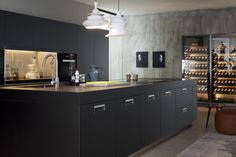 ARCLINEA Italia cabinets in Black Armour + Black Armour countertops with a Vina wine storage unit on the rear wall.