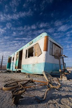 Abandoned trailer and fallen rusted bycicle at Salton Sea Beach in Southern California