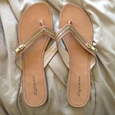 Lightly worn tan flip flops Super cute flip flops with zippers! Zippers don't unzip. Lightly worn! No signs of wear on the top! Could for a 10.5-11 Zigi Soho Shoes
