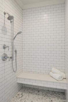 Clad in white subways, this well designed walk in shower features a polished nickel exposed plumbing shower head and sprayer.