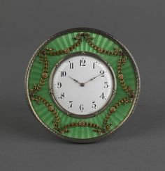 A SILVER-GILT AND GREEN GUILLOCHÉ ENAMEL DESK CLOCK BY FABERGÉ, WORKMASTER MIKHAIL PERKHIN. Circular, enamelled in translucent green over a sunburst guilloché ground, applied with ribbon-tied and gem-set leaf and rosette festoons, centering a white enamel dial within a bound, reeded bezel.